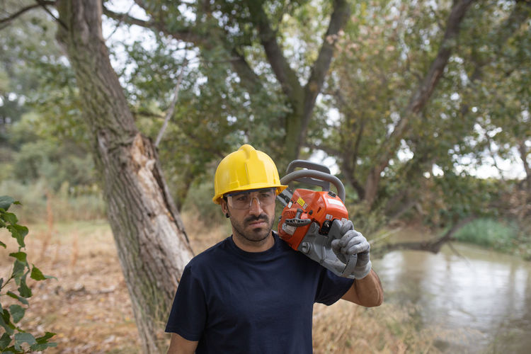 Man wearing hardhat carrying chainsaw in forest