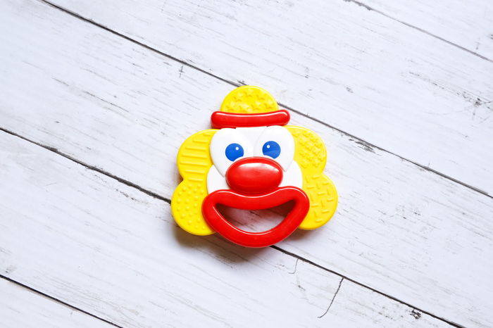Top view of baby teething or rattles in clown look on white wooden background. Toys Newborn Baby Toddler  Teething Clown Joker Happy Bite Plastic Multi Colored Red Yellow White Smile Birds View Top View Desk Table Celebration No People Wood - Material Indoors  Sweet Food