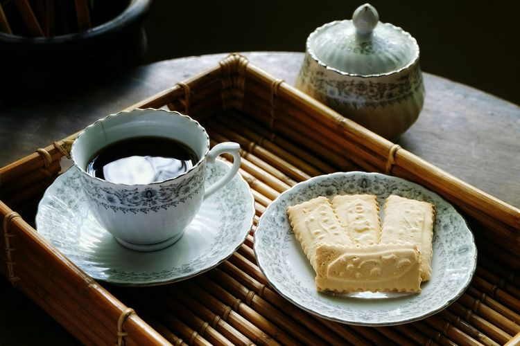 High Angle View Of Black Coffee With Crackers Served In Tray On Table