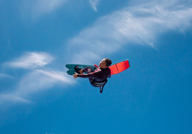 Low angle view of man surfboarding against blue sky