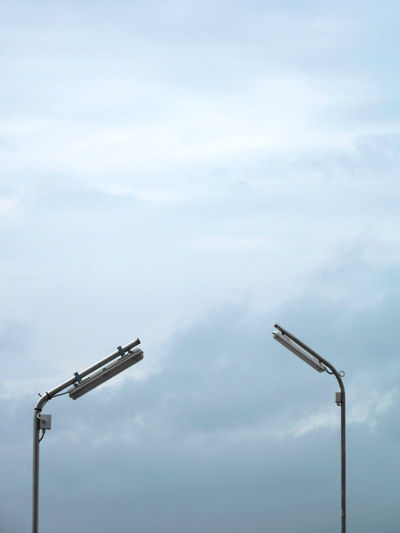 Two street lamps against cloudy sky backgorund Cloud - Sky Sky Low Angle View No People Day Industry Nature Lighting Equipment Outdoors Construction Industry Machinery Light Copy Space Technology Street Street Light Metal Control Pole Construction Equipment