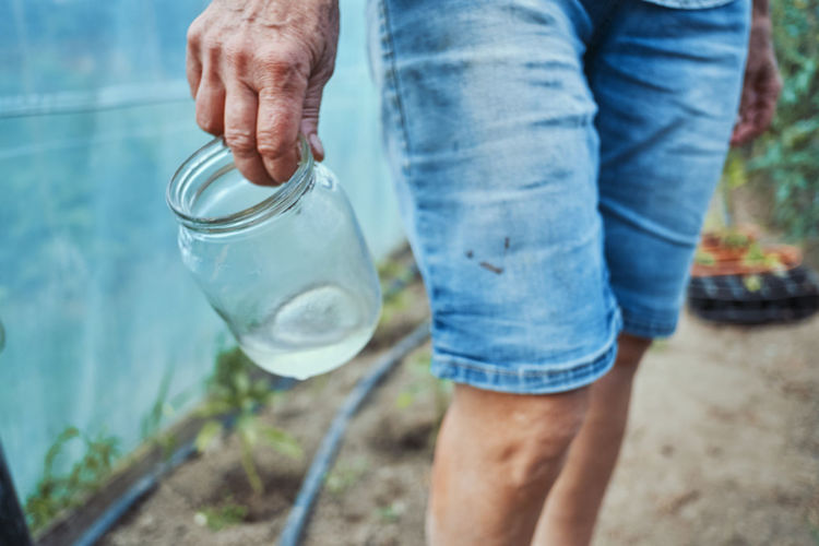 Midsection of woman holding container with water