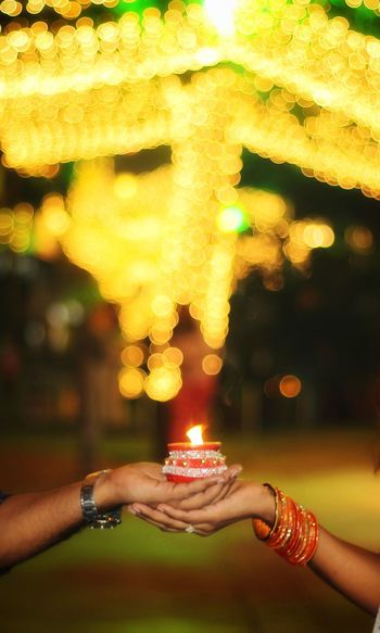 Cropped hands of couple holding lit diya against illuminated lights at night