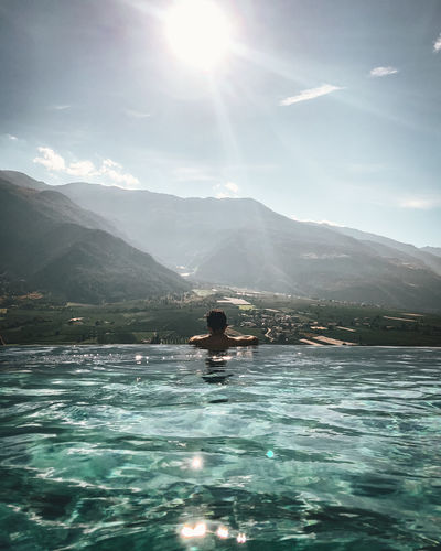 Mountain Water Beauty In Nature Sky One Person Scenics - Nature Leisure Activity Lifestyles Mountain Range Nature Sunlight Sunbeam Real People Lens Flare Day Waterfront Sun Holiday Tranquility Outdoors Bright Swimming Pool