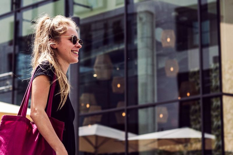 Low angle view of smiling young woman walking in city