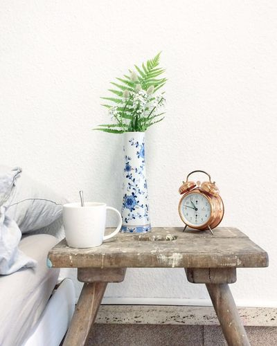 Clock And Vase On Wooden Table Against Wall