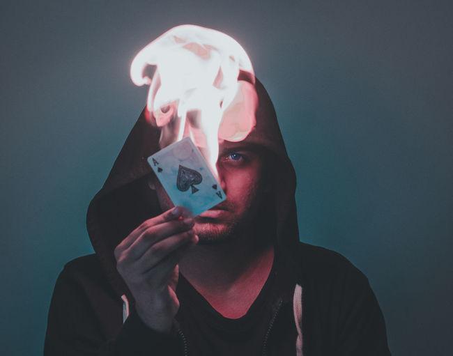 Portrait of man burning card