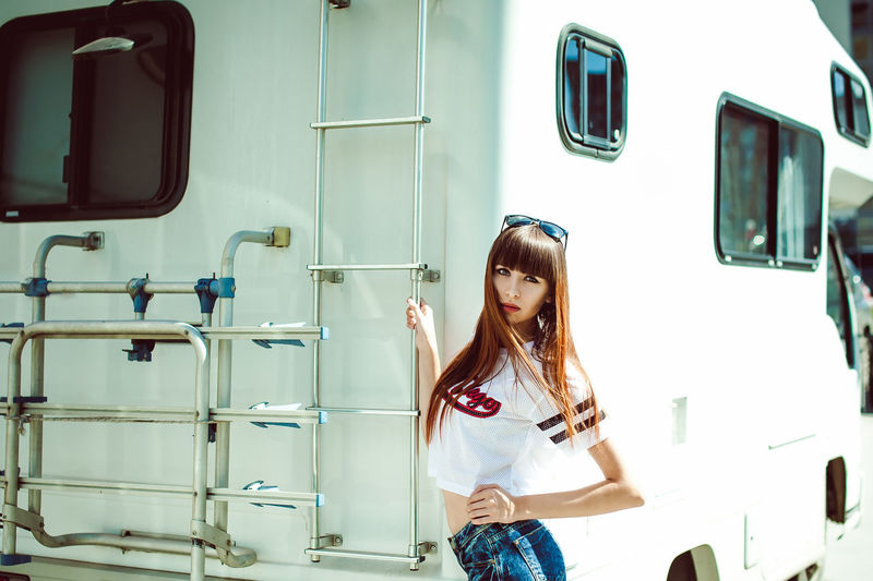 portrait attractive women in sports white T-shirt against background of Camper Trailer, transport for travel Day Front View Lifestyles One Person Outdoors Real People Standing Young Adult Young Women An Eye For Travel