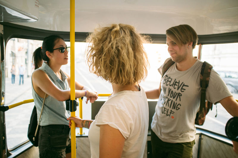 Friends talking while standing in bus