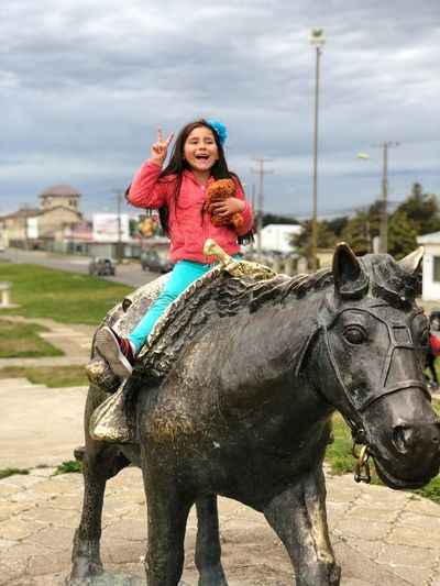 Happy Girl Showing Peace Sign While Sitting On Horse Sculpture