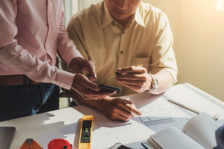 Midsection of businessmen using phone at desk in office