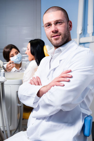 Friendly male dentist, assistant and smiling patient at dental clinic Dental Dentist Dentistry Doctor  Looking At Camera Medicine Teamwork Uniform Work Assistant Brunette Cabinet Confident  Dental Clinic Handsome Healthcare And Medicine Indoors  Male Medical Patient Professional Occupation Stomatology Teeth Tooth Women