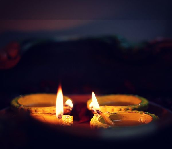 Close-up of lit candles burning in the dark