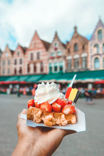 Cropped Image Of Hand Holding Dessert Against Buildings