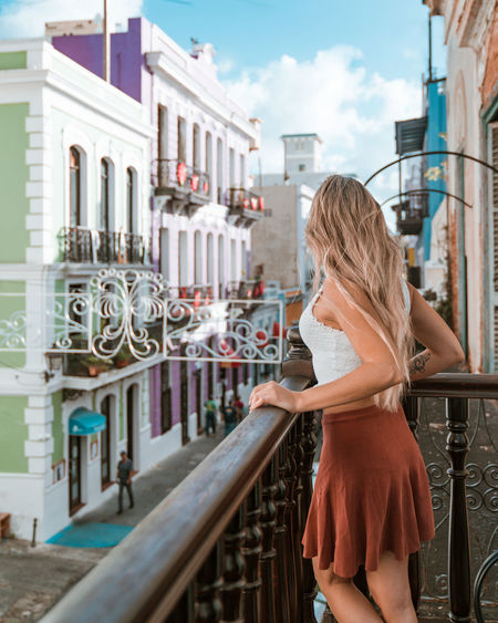 Woman standing by railing while looking outdoors