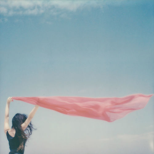 Rear view of woman holding sarong against sky