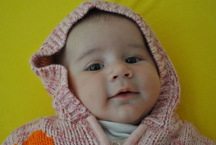 Cute baby girl wearing knitted warm clothing lying on bed