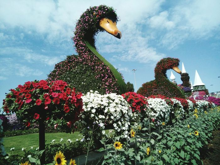 Low angle view of statues and flowers growing against sky in park