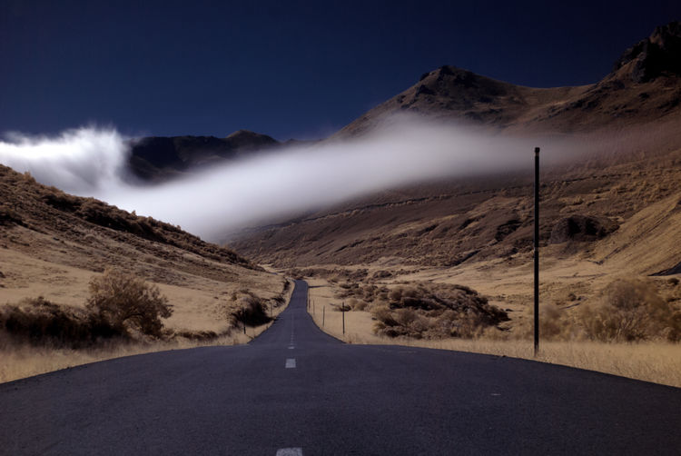Vanishing point road and fog in the background in a desolate mountain landscape Cloud Desolate Misty Beauty In Nature Clear Sky Day Diminishing Perspective Fog Foggy Landscape Mist Mountain Mountain Range Mountains Nature No People Outdoors Road Scenics Sky The Way Forward Tranquil Scene Transportation Vanishing Point