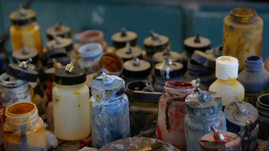 A bunch of used airbrush paint jars. Airbrush Paint Colors Jars  Paint Jars Air Compressor Artist Art Messy Dripping Dried Close-up Painting Supplies Brush