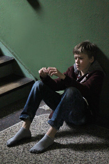 Annoyed Boy Boys Casual Clothing Communication Disagreement Dispute Education Floor Full Length Indoors  One Person Sitting Stairs Struggle Thinking Thinking About Life