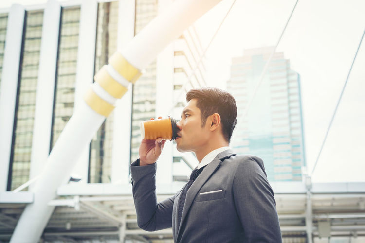 Side view of businessman drinking coffee by buildings in city