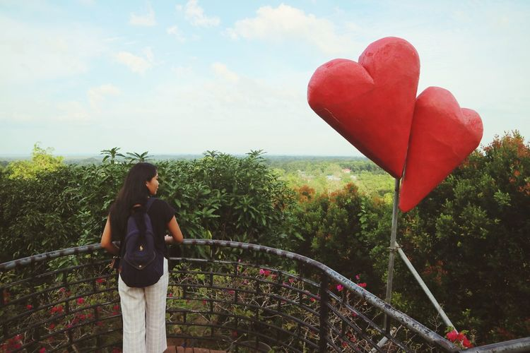 Woman holding umbrella standing by heart shape against sky