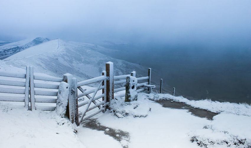 High angle view of snow covered railing on mountain against sky