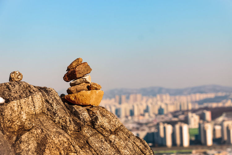 Stone balancing atop a fortress overlooking a city