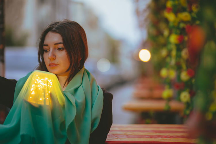 Thoughtful beautiful woman holding scarf and glowing jar in city at dusk