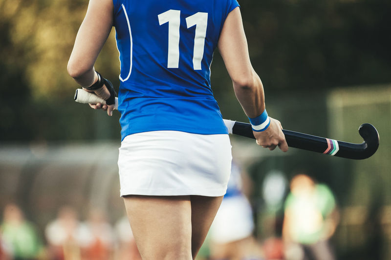 Young hockey player woman with ball in attack playing field hockey game Field Hockey Review Field Hockey Woman Active Adult Athlete Ball Blue Clothing Competition Day Effort Focus On Foreground Front View Incidental People Leisure Activity Midsection One Person Real People Shorts Sport Sports Clothing Sports Uniform Sportsman Team Three Quarter Length