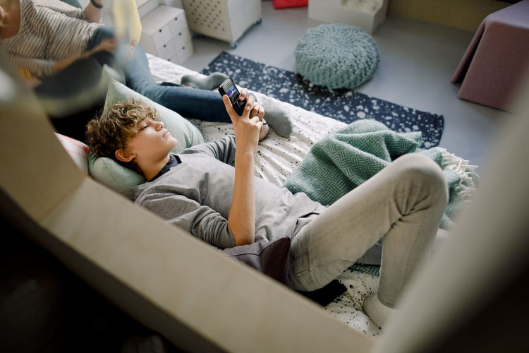 Rear view of boy using mobile phone at home