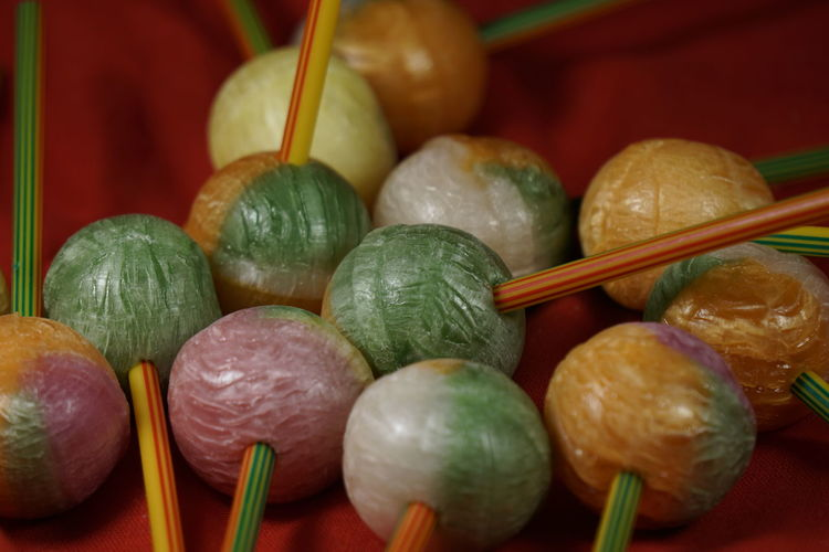 Close-up of lollipops on red fabric