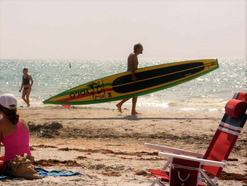 Man carrying a surfboard, Indian Rocks Beach, FL- YOLO! Beach Florida Fun In The Sun Indian Rocks Beach, FL Man Man On Beach On The Beach Outdoors Shore Sports Summer Surf Surf Life Surf's Up Surfboard Surfer Surfing Tourism Vacations Walking On The Beach Water Yolo People And Places Gulf Of Mexico Enjoying Life
