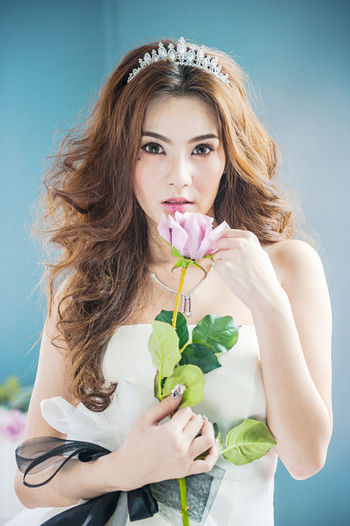 Portrait of beautiful bride holding rose standing at home
