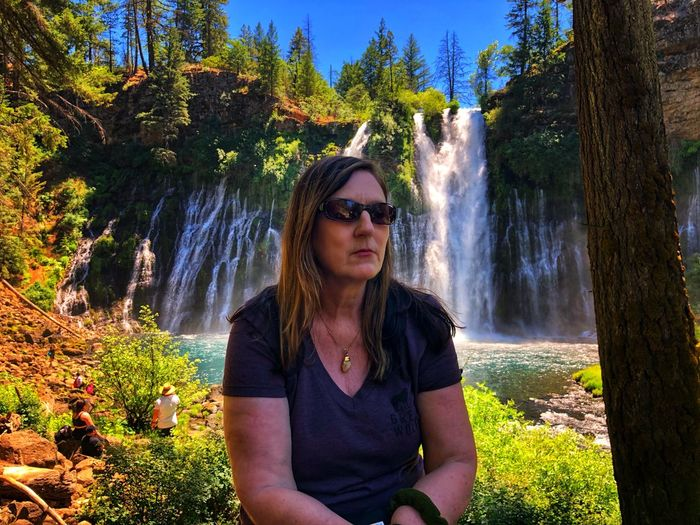 Beautiful woman wearing sunglasses while sitting against waterfall in forest