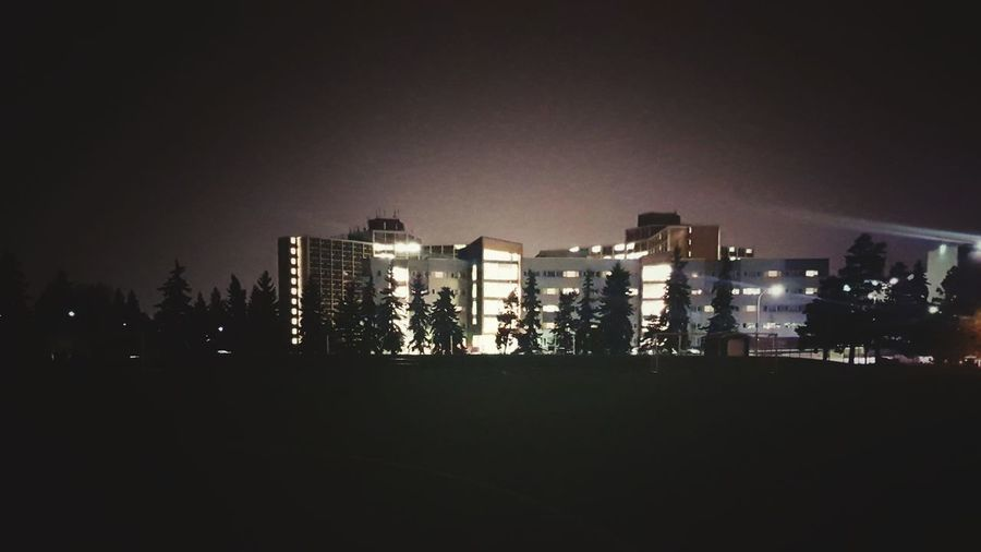 Silhouette buildings against sky at night