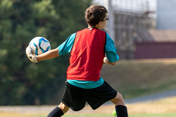 Rear view of boy playing soccer goalkeeper preparing to throw soccer ball