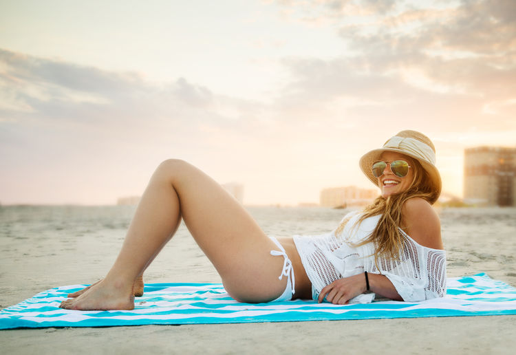 Young woman relaxing on sand at beach against sky