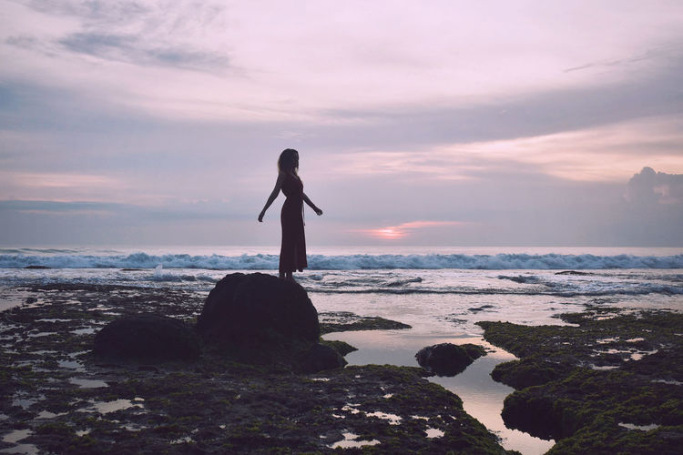 Woman standing on rock at beach against sky during sunset