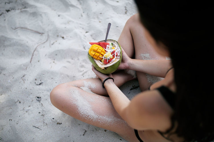 High angle view of woman having fruits while sitting on sand