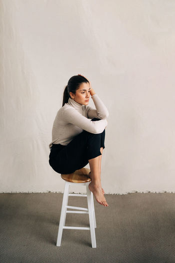 Side view of young woman sitting on chair against wall