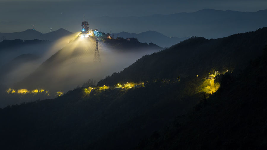 Scenic view of illuminated mountain against sky at night