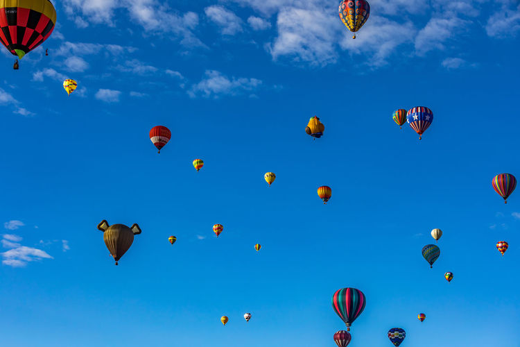 Hot Air Balloons fly over the city of Albuquerque, New Mexico during the mass ascension at the annual International Hot Air Balloon Fiesta in October, 2016 Ballooning Festival Blue Celebration Cloud - Sky Day Flying Hot Air Balloon Low Angle View Mid-air Multi Colored No People Outdoors Sky Traditional Festival Transportation