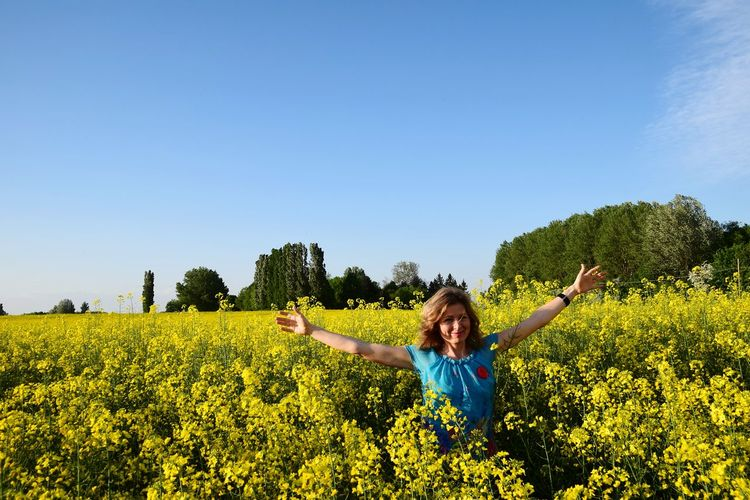 Full length of happy young woman with arms raised on field against sky