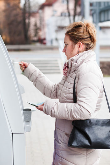 Woman drawing out money from ATM Account Atm Bank Banking Card Cash Cashier Machine Credit Debit Deposit Draw Drawing Finance Financial Holding Machine Money Outdoors Technology Terminal Using Wallet Withdraw Withdrawing Cash Woman