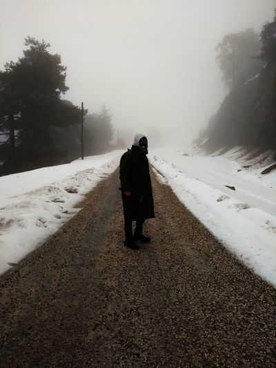 Full length of man wearing warm clothing while standing amidst road by snow during foggy weather