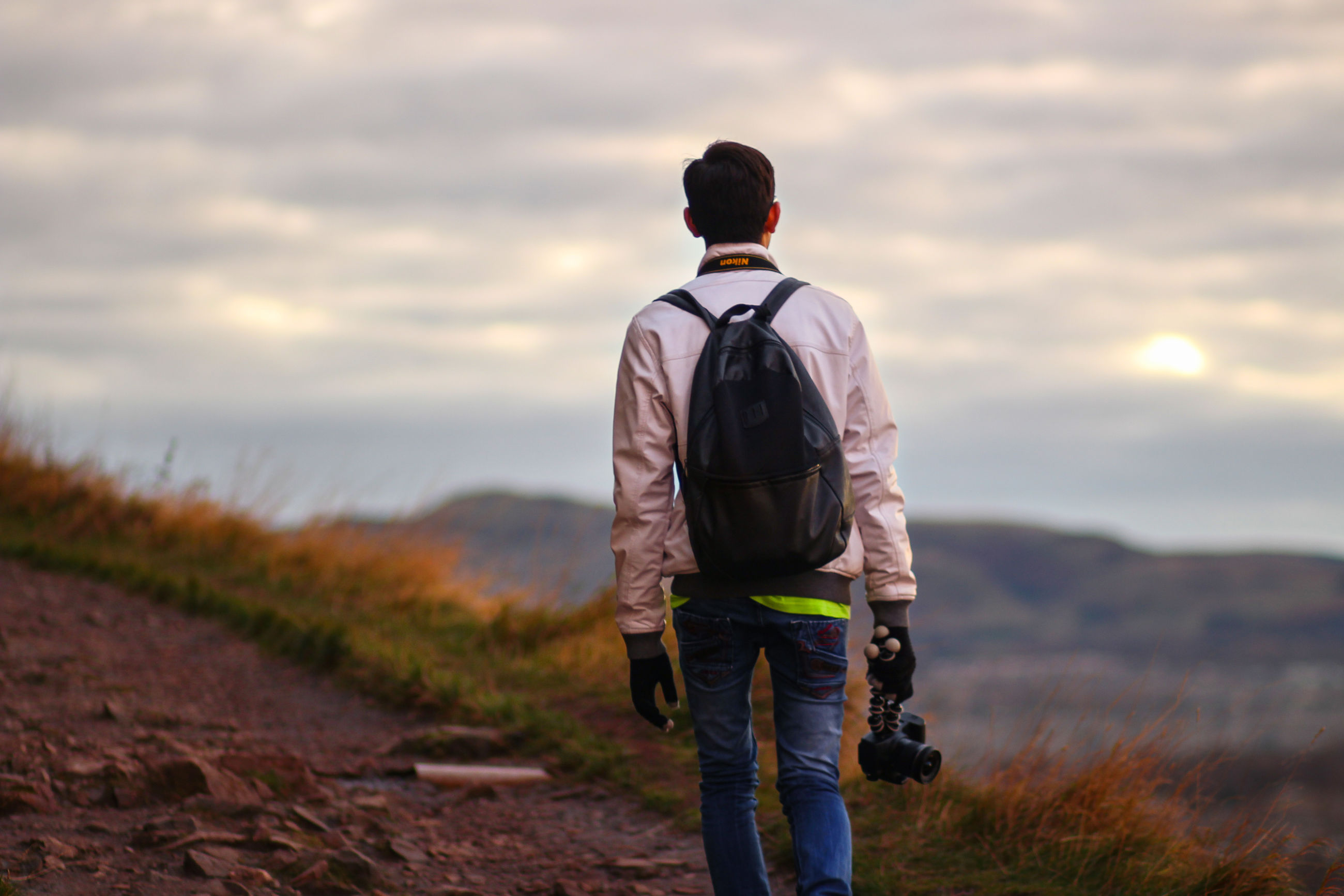sky, rear view, cloud - sky, one person, men, nature, real people, casual clothing, land, leisure activity, lifestyles, beauty in nature, three quarter length, field, standing, scenics - nature, grass, non-urban scene, day, outdoors, jeans