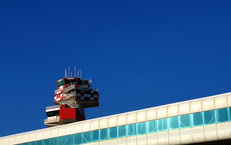 Low angle view of airport tower and building against clear blue sky