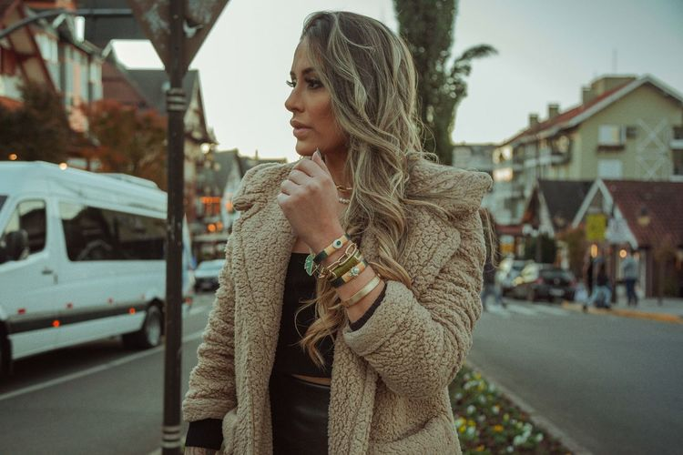 Young woman looking away while standing on street in city